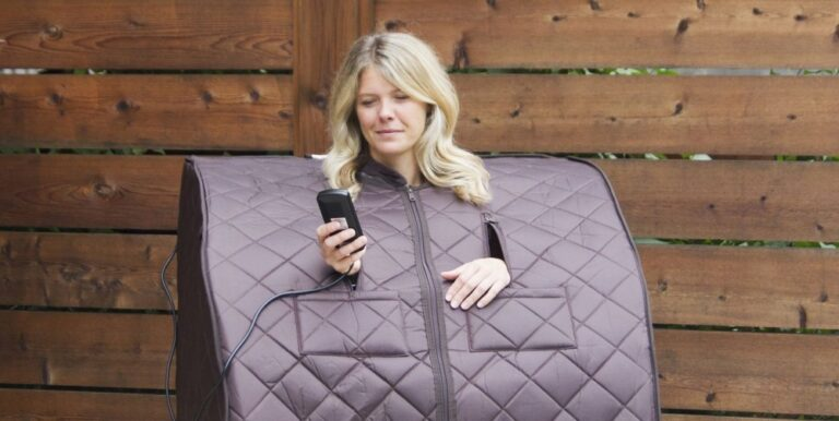 woman using phone while sitting inside a portable steam sauna