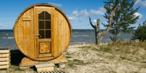 an outdoor sauna with a lake behind
