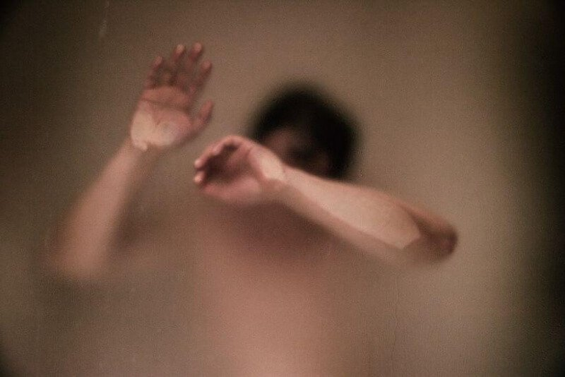 naked man against a sauna glass with smoke inside
