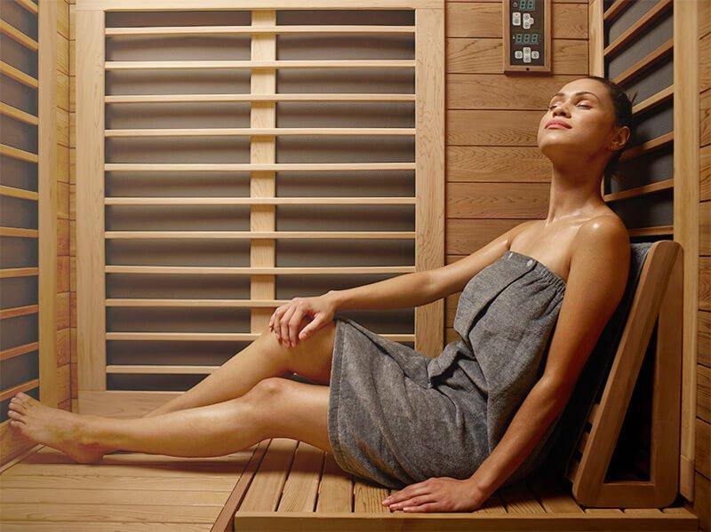 sweating woman inside an infrared sauna
