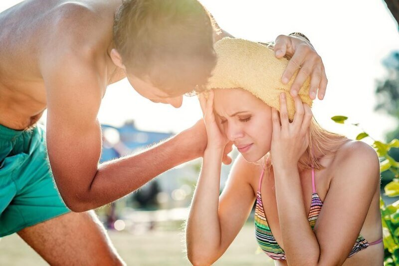 a man helping a woman dehydrate with a wet towel