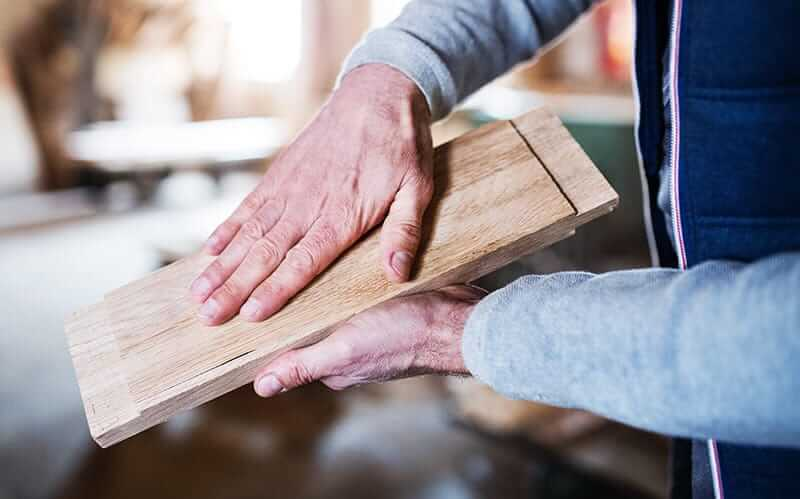 man feeling a piece if wood