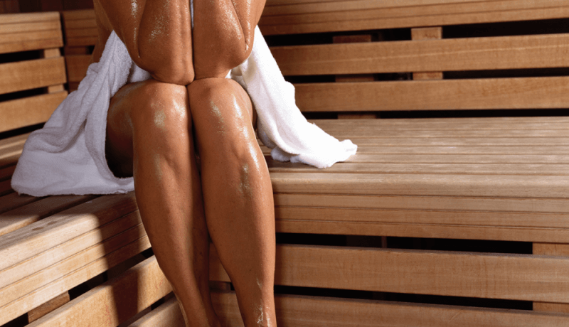 sweaty woman sitting inside a sauna